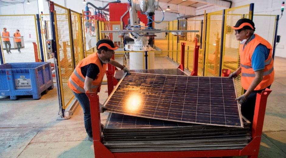 Photo of workers carrying solar panels at the first French factory specializing in the recycling of solar photovoltaic panels in Rousset, southern France.