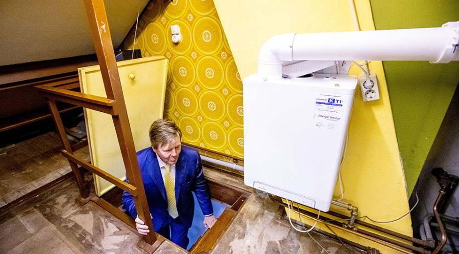 The King of the Netherlands, Willem-Alexander, climbs a staircase that leads to the attic of a house