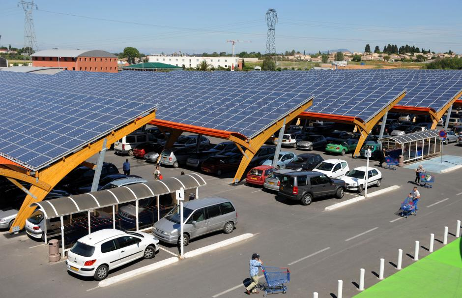 A photo of a supermarket in the south of France. Its parking lot is sheltered by canopies with solar PV panels.