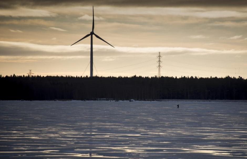 A man walks on the frozen Baltic Sea in front of a wind turbine, on January 25, 2018 in Vaasa, western Finland.