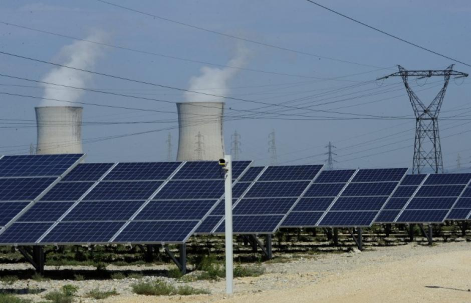 Photo of photovoltaic panels in front of the cooling towers of the Tricastin nuclear power plant in Provence.