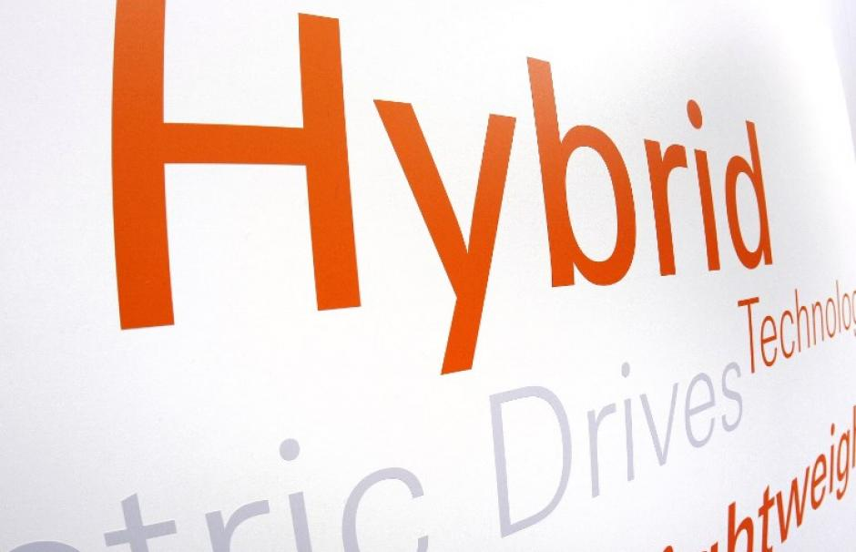 "Image showing a ""hybrid"" logo at the North American International Auto Show, known as the Detroit Auto Show."
