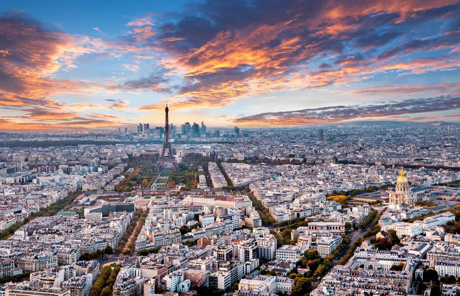 An aerial photograph of Paris with the La Défense business district in the distance.