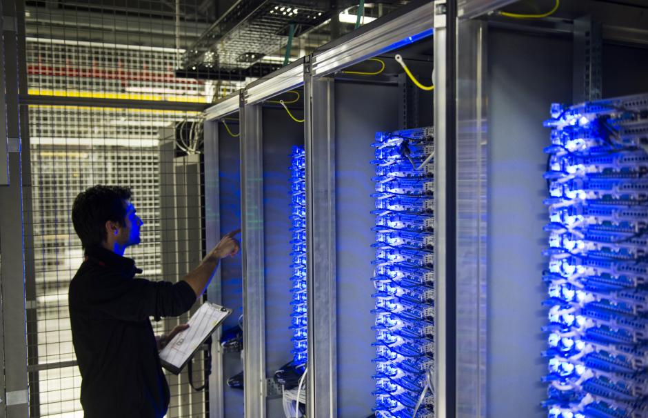 Photo of a technician working on hard drives in a data storage center in the suburbs of Paris.