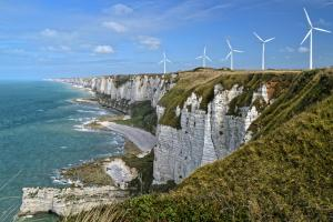 Image of wind turbines on the crest of a cliff, a sign of the rise of renewable energies in Europe.