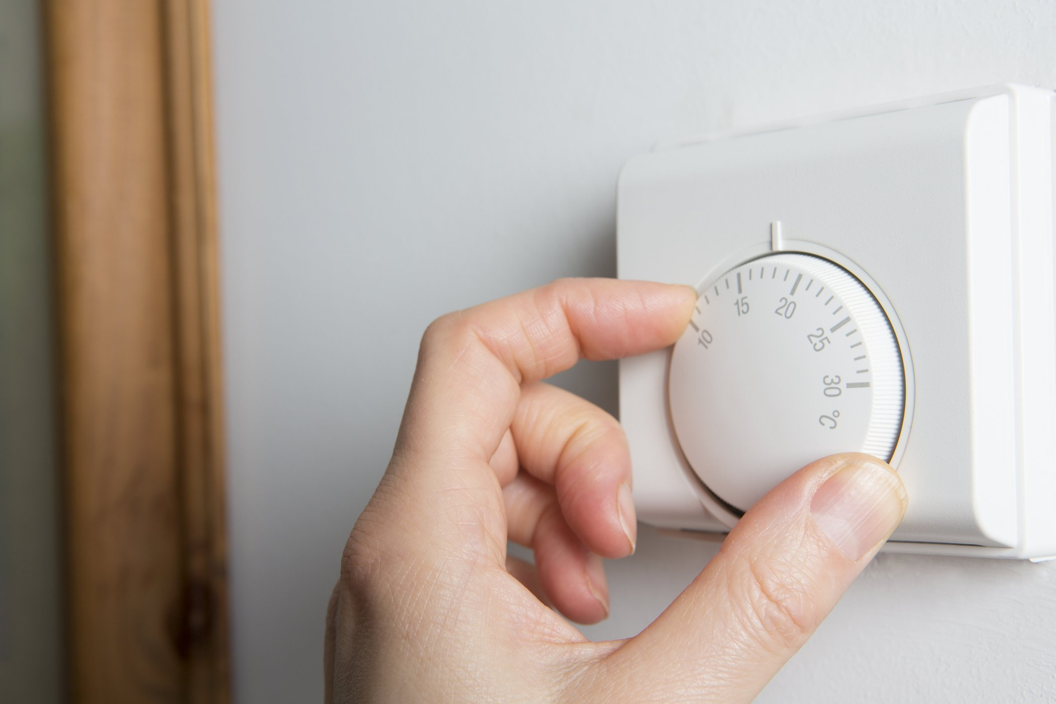 Close-up of one hand on using a thermostat